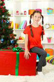 Little girl with large gift box near christmas tree — Foto de Stock