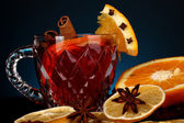 Fragrant mulled wine in glass with spices and oranges around on blue background — Stock Photo