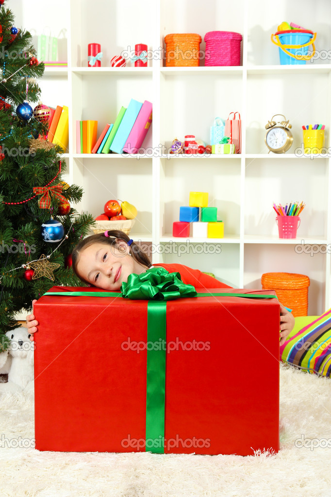 Little girl with large gift box near christmas tree — Stock Photo #15529191
