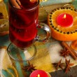 Fragrant mulled wine in glass with spices and oranges around on wooden table - Zdjęcie stockowe