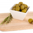 Green olives in white bowl with rosemary on board isolated on white - Stock Photo