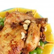 Whole roasted chicken with grapes, oranges and spices on blue plate on white background close-up - Stock Photo