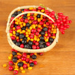 Colorful autumn berries in wicker basket on wooden background close-up - Stock Photo