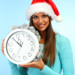 Beautiful young woman with clock, on blue background — Stock Photo #15633407