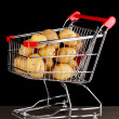 Ripe potatoes in trolley on wooden table on black background - Stock Photo