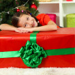 Stock Photo: Little girl with large gift box near christmas tree