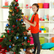 Little girl decorating christmas tree - Stok fotoğraf