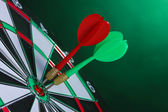 Tablero de dardos con dardos sobre fondo verde — Foto de Stock