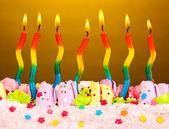 Pastel de cumpleaños con velas sobre fondo marrón — Foto de Stock