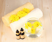 Vase with yellow flowers, spa setting on wooden background — Stock Photo