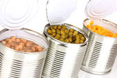 Open tin cans of corn, beans and peas isolated on white — Stock Photo