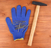 Hammer and glove on wooden background — Photo