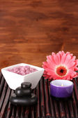 Composition of spa stones, bath salt, candle and gerbera on bamboo mat on wooden background — Stock Photo