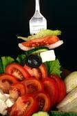 Tasty greek salad on black background close-up — Stock Photo