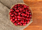 Fresh cornel berries in wicker basket on wooden background close-up — Stock Photo