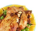 Pollo asado entero con uvas, naranjas y especias en placa azul en primer plano de fondo blanco — Foto de Stock