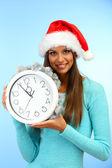 Giovane e bella donna con orologio, su sfondo blu — Foto Stock