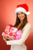 Beautiful young woman with gifts, on red background — Stock Photo