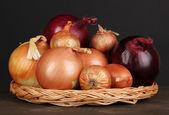 Dojrzałe cebuli na kołyski wiklinowe na drewnianym stole na czarnym tle — Zdjęcie stockowe