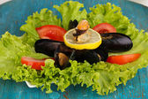 Snack of mussels and lemon on plate on blue wooden table — Stock Photo