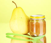 Useful and tasty baby food with pear and spoon on green background — ストック写真