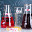 Test-tubes with various acids and other chemicals on the background of the blackboard — Stock Photo #15665951
