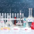 Test-tubes with various acids and other chemicals on the background of the blackboard — Stock Photo #15665977
