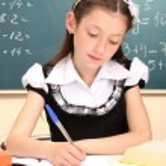 Little schoolchild in classroom write in notebook — Stock Photo #15666203