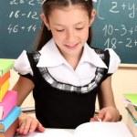 Beautiful little schoolgirl in classroom reading the book — Stock Photo #15666209
