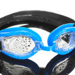 Blue swim goggles with drops on grey background — Stock Photo