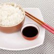 Stock Photo: Bowl of rice and chopsticks on plate on grey mat