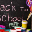The words 'Back to School' written in chalk on the small school desk with various school supplies close-up — Stock Photo #15668123