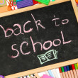 The words 'Back to School' written in chalk on the small school desk with various school supplies close-up — Stock Photo #15668183