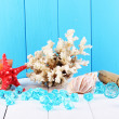 Decor of seashells on wooden table on blue wooden background — Stock Photo #15668551