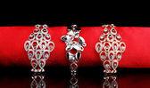 Trois bracelets élégants sur le chiffon rouge sur fond noir — Photo