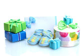 Beautiful gifts, baby's bootees, blank postcard and dummy isolated on white — Stock Photo