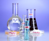 Test-tubes with various acids and chemicals on violet background — 图库照片