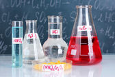 Test-tubes with various acids and other chemicals on the background of the blackboard — Stockfoto