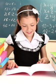 Beautiful little schoolgirl in classroom reading the book — Stock Photo