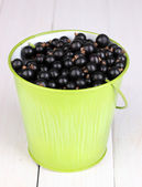 Black currant in metal bucket on wooden background — Stock Photo