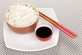 Bowl of rice and chopsticks on plate on grey mat — Stock Photo