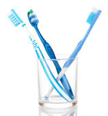 Toothbrushes in glass isolated on white — Stock Photo