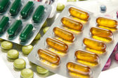 Capsules and pills packed in blisters, close up — Stock Photo