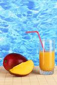 Ripe appetizing mango on woven napkin on water background — Stock Photo