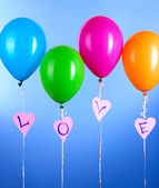 Colorful balloons keeps word love on blue background — Stock Photo