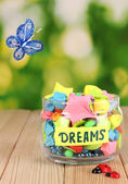 Glass vase with paper stars with dreams on wooden table on natural background — Stock Photo