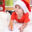 Little boy in Santa hat writes letter to Santa Claus — Stock Photo #15675469