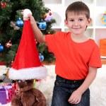 Little boy in Santa hat sits near Christmas tree — Stock Photo #15675559