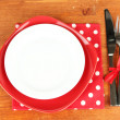Empty red and white plates with fork and knife on wooden table, close-up — Stock Photo