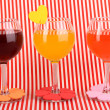 Stock Photo: Colorful cocktails with bright decor for glasses on red background with stripes
